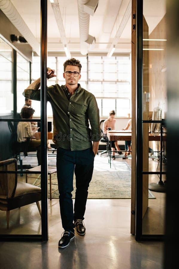 Junger Mann, der im Eingang im Startbüro steht stockfotografie