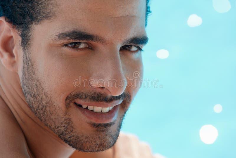 Junger Mann, der im Swimmingpool sitzt lizenzfreie stockbilder
