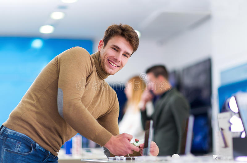 Junger Mann, der intelligentes Telefon im Speicher wählt lizenzfreies stockfoto