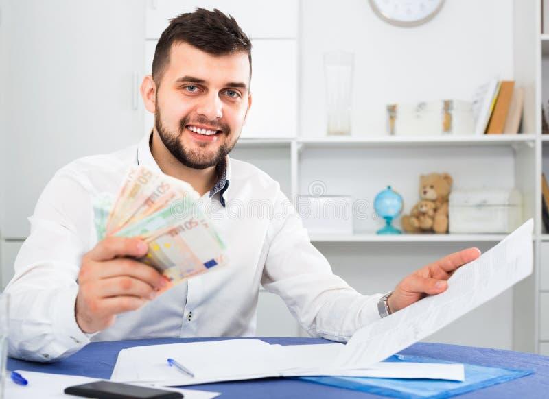 Junger Mann, der kämpft, um Stromrechnungen und Miete für seine Wohnung zu zahlen lizenzfreies stockfoto