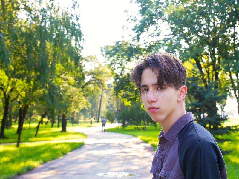 Junger Mann, der Kamera betrachtet Porträt des jugendlich Jungen, außerhalb des Porträts im Park stockbild