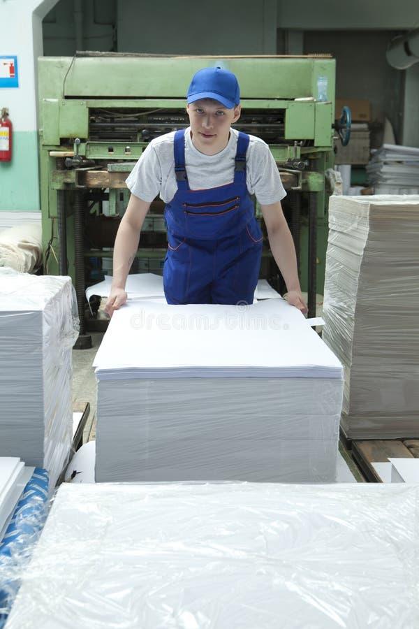 Junger Mann in der Kappe, die in der Druckfabrik arbeitet lizenzfreie stockfotografie