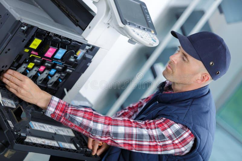 Junger Mann in der Kappe, die an Offsetdruckmaschine arbeitet stockfotos