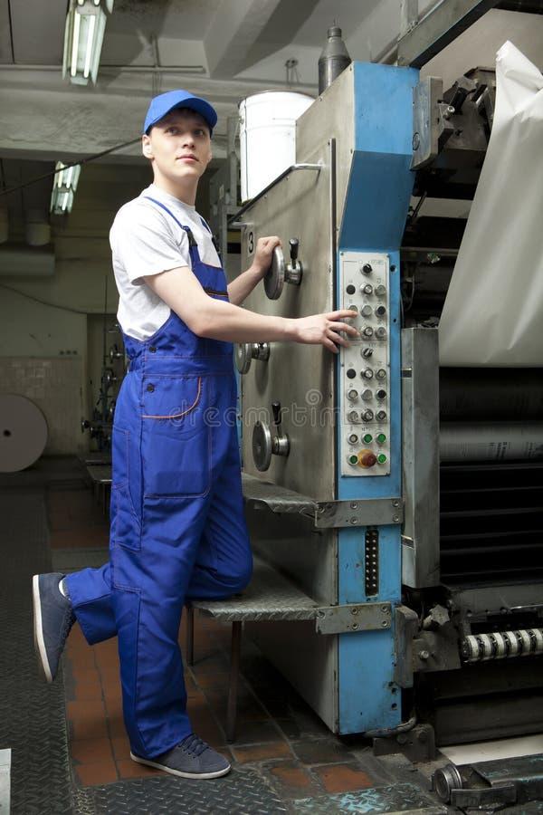 Junger Mann in der Kappe, die an Offsetdruckmaschine arbeitet lizenzfreies stockfoto