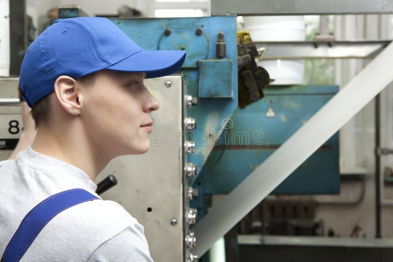 Junger Mann in der Kappe, die an Offsetdruckmaschine arbeitet stockbild