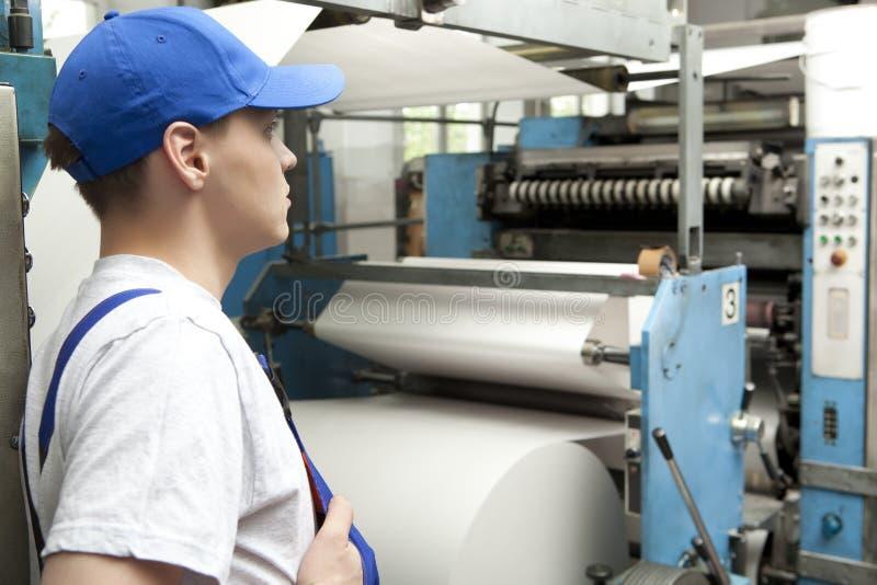 Junger Mann in der Kappe, die an Offsetdruckmaschine arbeitet lizenzfreie stockfotos