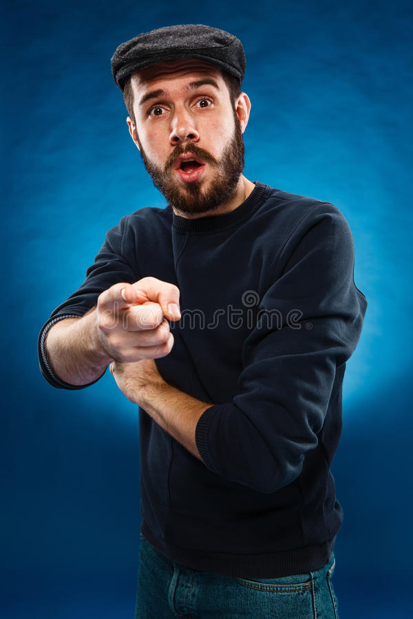 Junger Mann in der Kappe, Finger zeigend in Richtung zur Kamera stockbild