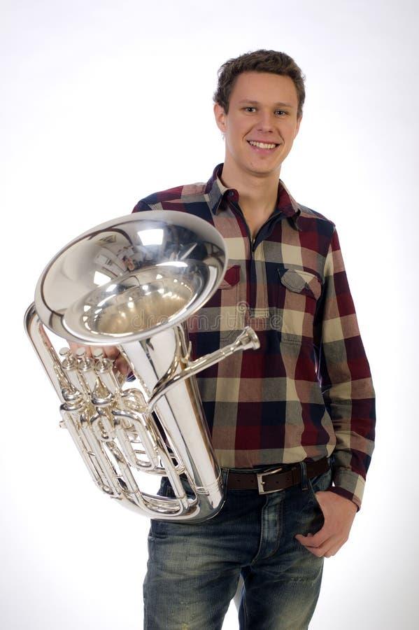 Junger Mann in der Klage, die eine Trompetehupe anhält lizenzfreie stockfotografie
