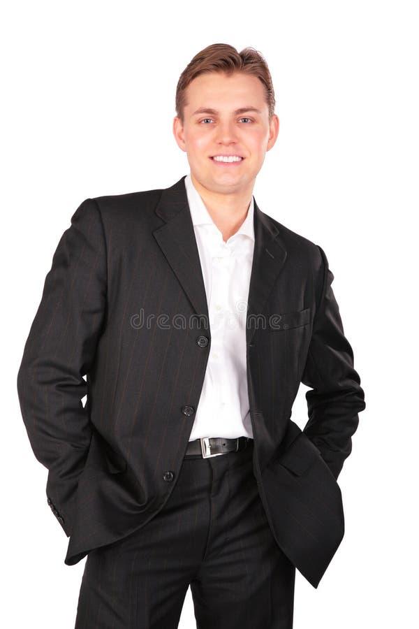 Junger Mann in der Klage, die Hände in den Taschen aufwirft lizenzfreie stockfotos