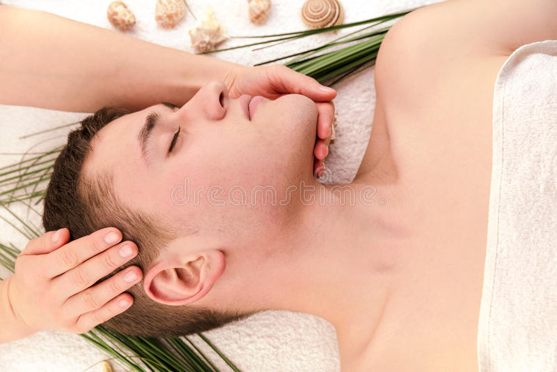 Junger Mann, der Kopfmassage im Badekurortsalon hat lizenzfreie stockbilder