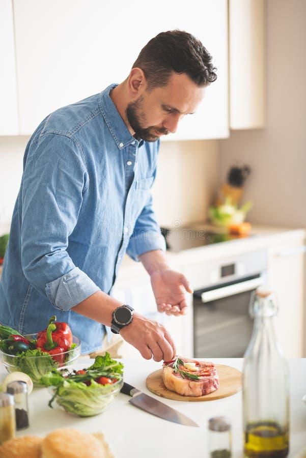 Junger Mann, der Kräuter Fleisch bei der Stellung nahe Küchentisch hinzufügt stockfotografie