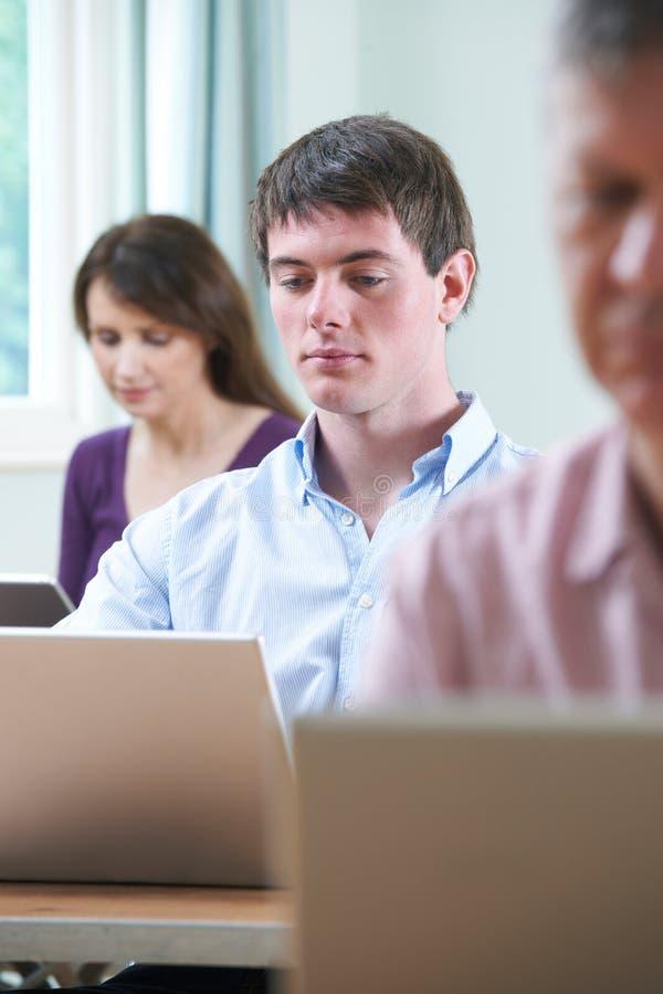 Junger Mann, der an Laptop in der Erwachsenenbildungs-Klasse arbeitet stockfotos