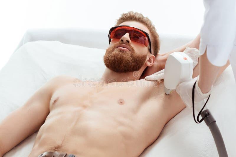 Junger Mann, der Laser-Hautpflege auf der Achselhöhle lokalisiert auf Weiß empfängt lizenzfreie stockfotos