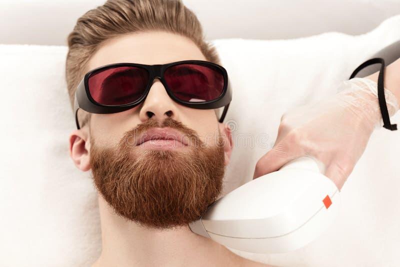 Junger Mann, der Laser-Hautpflege auf Hals empfängt stockbild