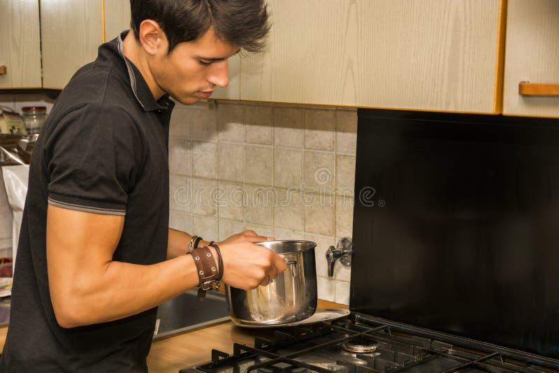Junger Mann, der Lebensmittel auf Ofen kocht stockfotografie