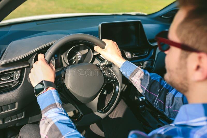 Junger Mann, der Lenkrad beim Fahren des Autos h?lt lizenzfreies stockbild