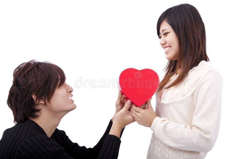 Junger Mann, der Liebesgeschenk zur Frau überreicht lizenzfreies stockfoto