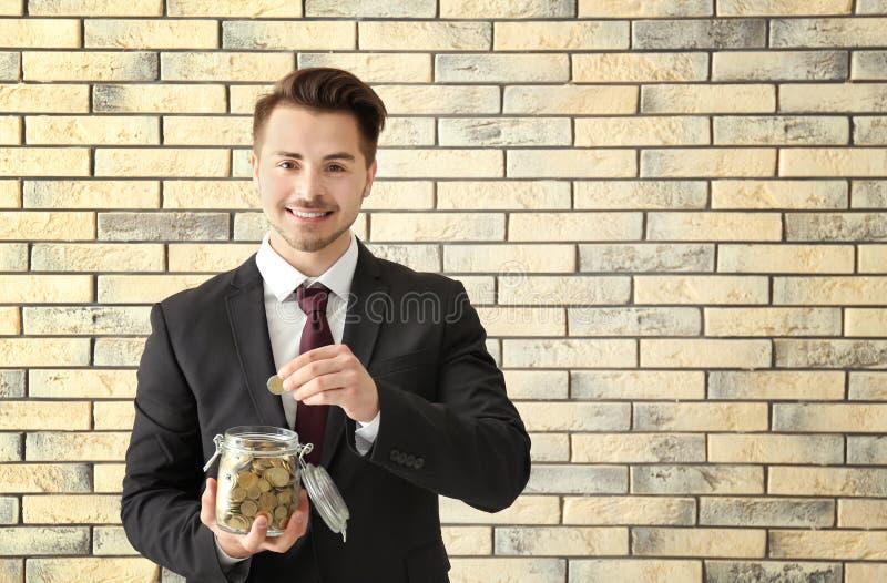Junger Mann, der Münze in Glasgefäß auf Ziegelsteinhintergrund setzt Einsparungensgeldkonzept stockfoto