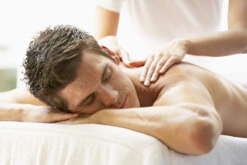 Junger Mann, der Massage am Badekurort genießt lizenzfreies stockbild