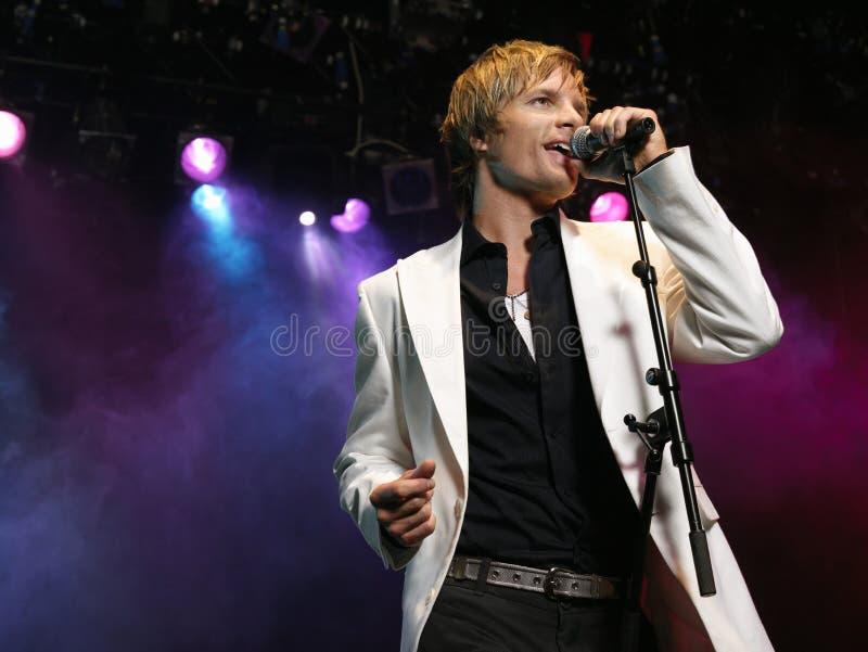 Junger Mann, der in Mikrofon singt lizenzfreies stockfoto