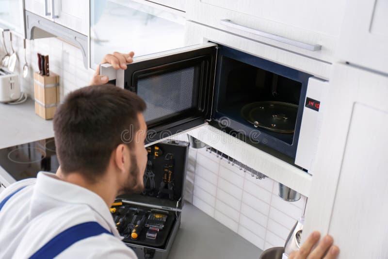 Junger Mann, der Mikrowellenherd repariert stockfotografie
