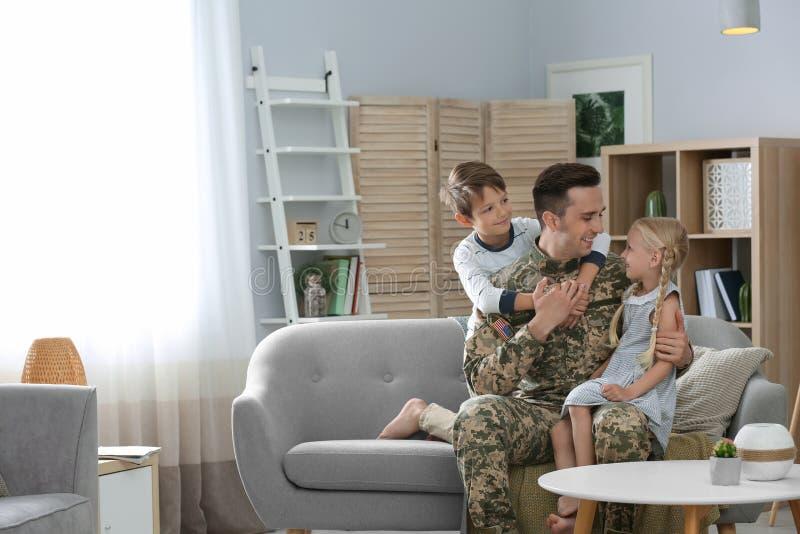 Junger Mann in der Militäruniform mit seinen Kindern lizenzfreie stockfotos