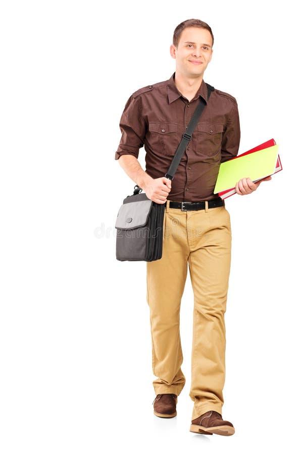 Junger Mann, der mit Büchern geht lizenzfreie stockbilder