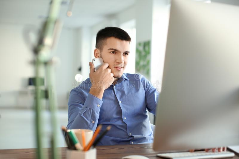 Junger Mann, der mit Computer arbeitet lizenzfreies stockbild