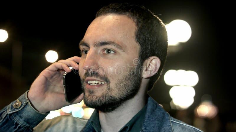 Junger Mann, der mit dem Handy geht an der Nachtstadt spricht stockfotos