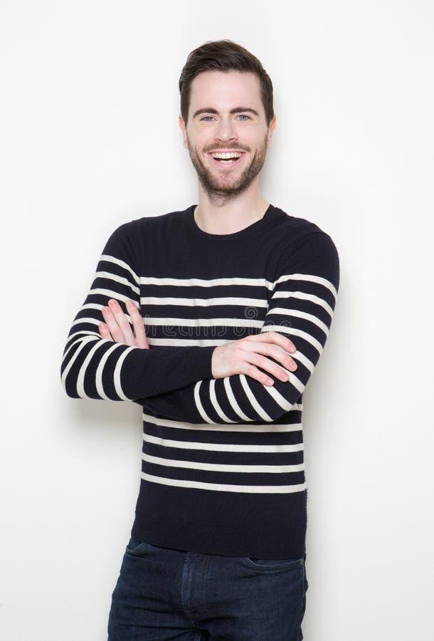 Junger Mann, der mit den Armen gekreuzt lächelt stockfotografie