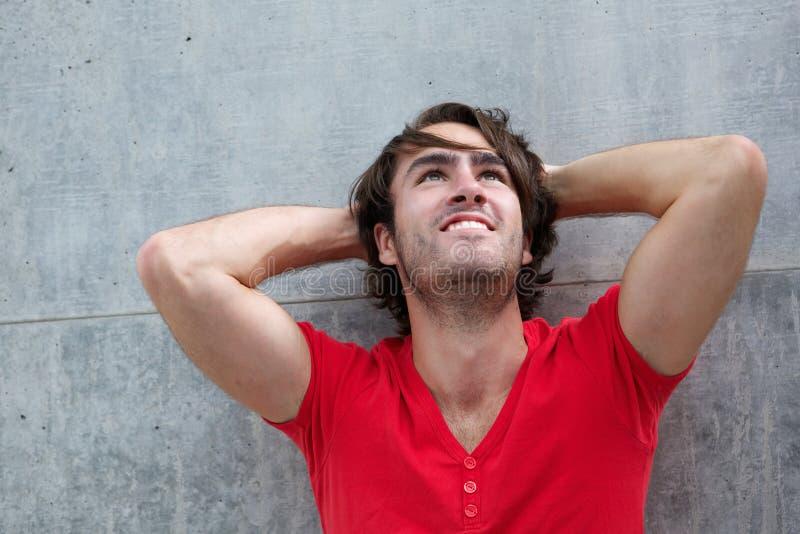 Junger Mann, der mit der Hand im Haar denkt stockfoto