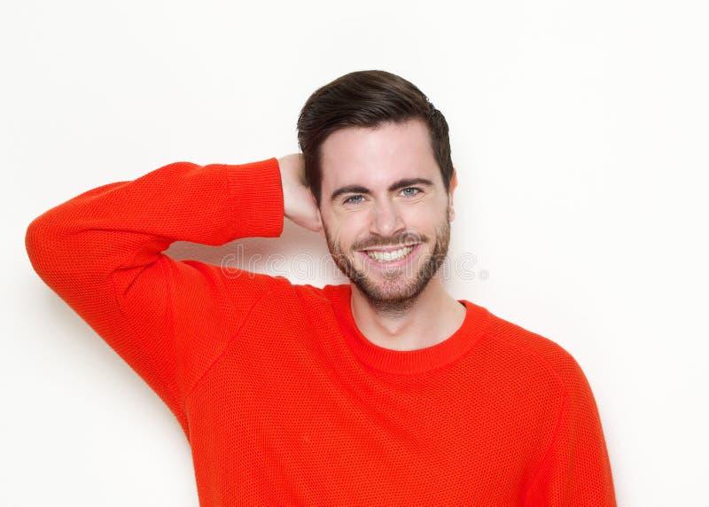 Junger Mann, der mit der Hand im Haar lächelt stockbild