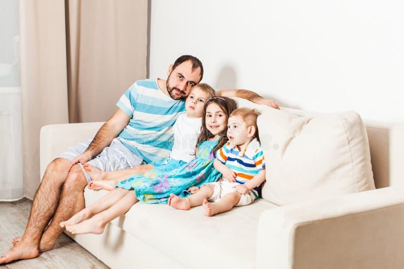 Junger Mann, der mit drei Kindern auf der Couch im Wohnzimmer sitzt stockfotografie
