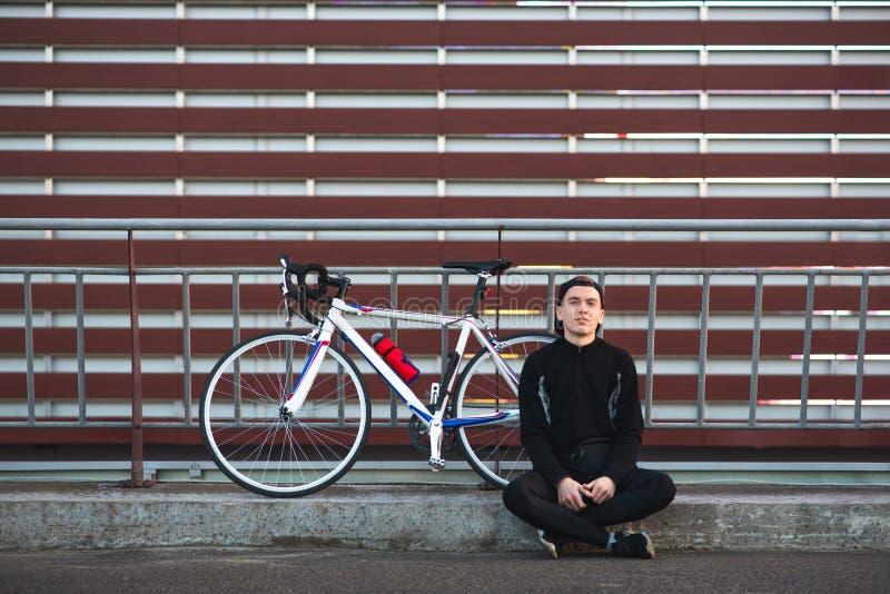 Junger Mann, der mit einem Fahrrad auf einem gestreiften Hintergrund, untersuchend die Kamera und das Lächeln sitzt stockfotos