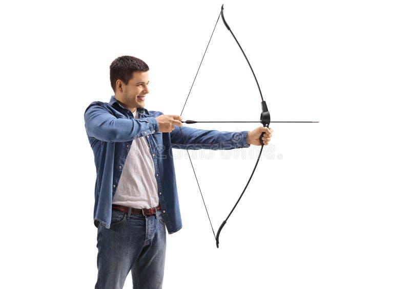 Junger Mann, der mit einem Pfeil und Bogen zielt stockbild