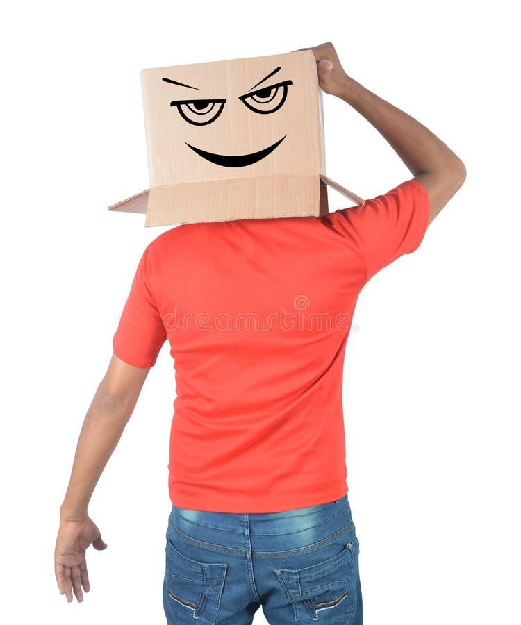 Junger Mann, der mit einem Sammelpack auf seinem Kopf mit smiley gestikuliert stockfotografie