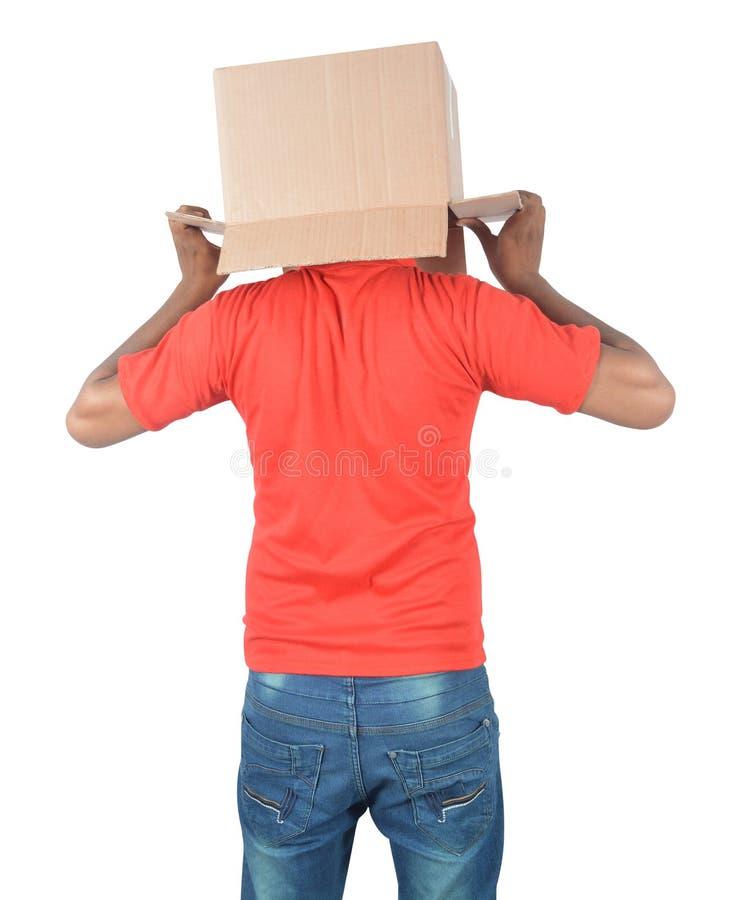 Junger Mann, der mit einer Pappschachtel auf seinem Kopf an lokalisiert gestikuliert stockfotos