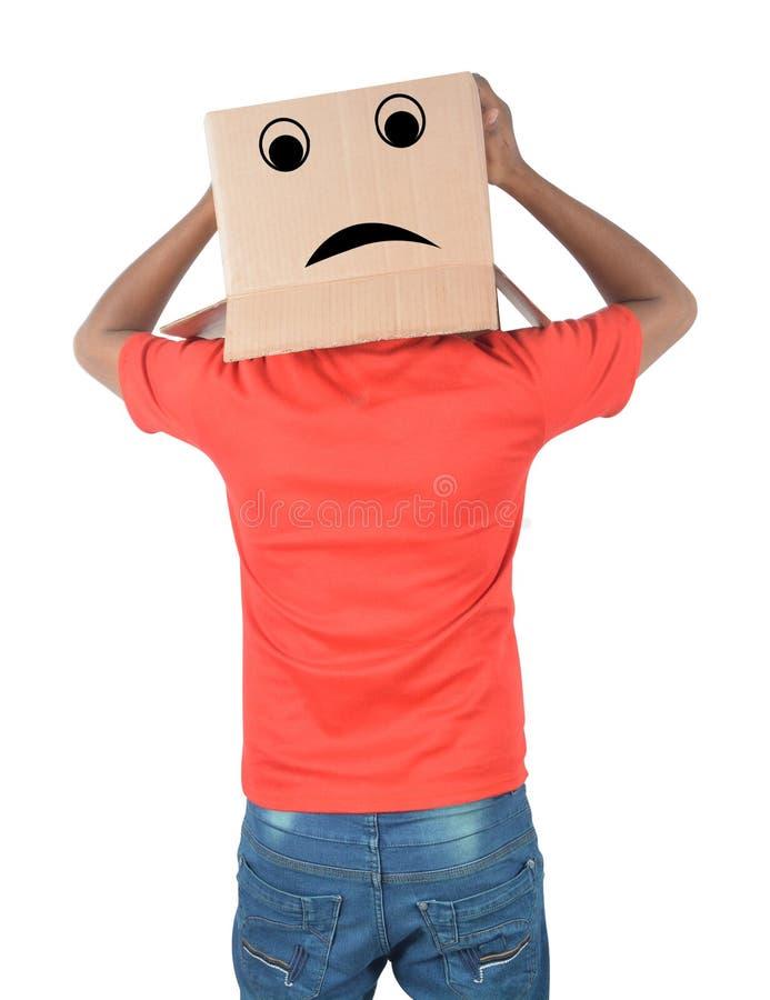 Junger Mann, der mit einer Pappschachtel auf seinem Kopf mit traurigem Fa gestikuliert stockbild