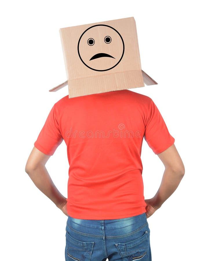 Junger Mann, der mit einer Pappschachtel auf seinem Kopf mit traurigem Fa gestikuliert lizenzfreie stockfotografie