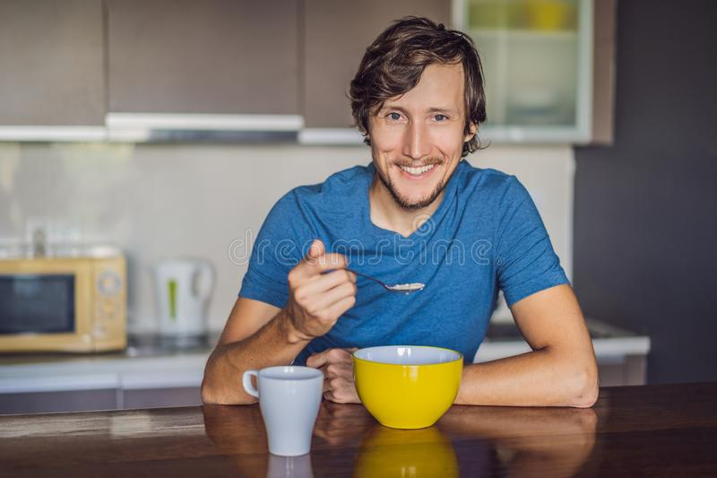 Junger Mann, der mit geschmackvoller Milch zu Hause fr?hst?ckt lizenzfreie stockfotografie