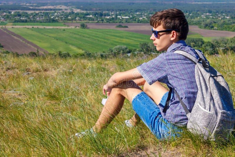 Junger Mann, der mit Rucksack sitzt und schöne Ansicht, Tourismuskonzept betrachtet lizenzfreie stockfotografie