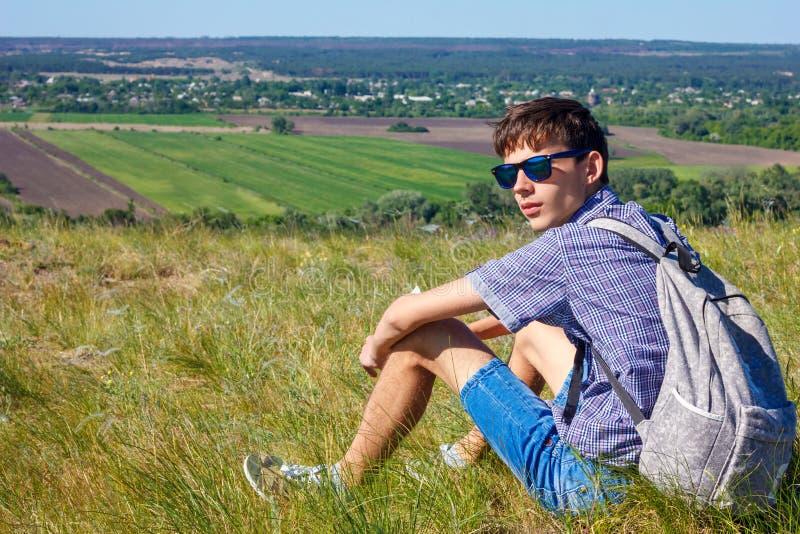 Junger Mann, der mit Rucksack sitzt und schöne Ansicht, Tourismuskonzept betrachtet stockbild