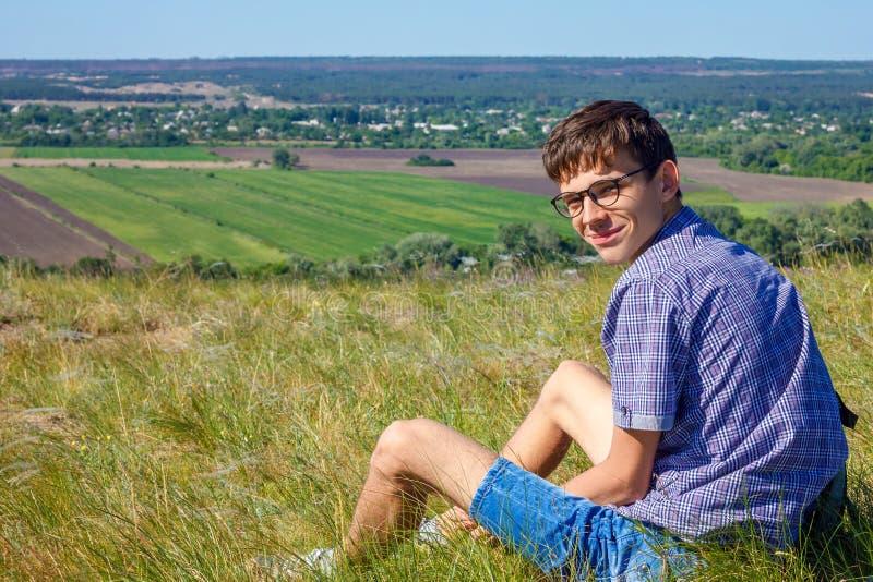 Junger Mann, der mit Rucksack sitzt und schöne Ansicht, Tourismuskonzept betrachtet stockfotografie