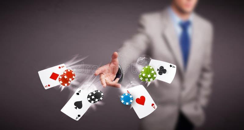Junger Mann, der mit Schürhakenkarten und -chips spielt stockfotos