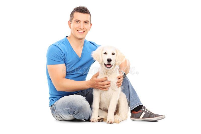 Junger Mann, der mit seinem Hund auf dem Boden sitzt stockbild
