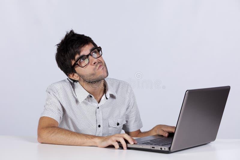 Junger Mann, der mit seinem Laptop arbeitet stockbilder