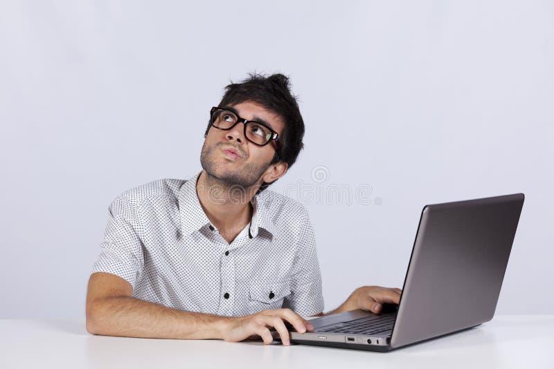 Junger Mann, der mit seinem Laptop arbeitet stockfotografie