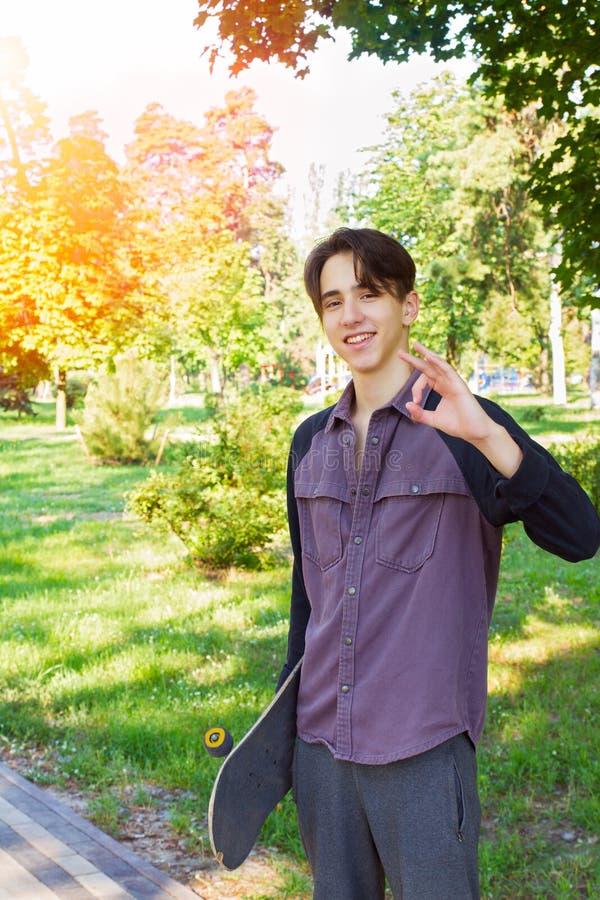 Junger Mann, der mit Skateboard in den Händen im Stadtpark steht Jugendlich Jungenschlittschuhläufer stockbild
