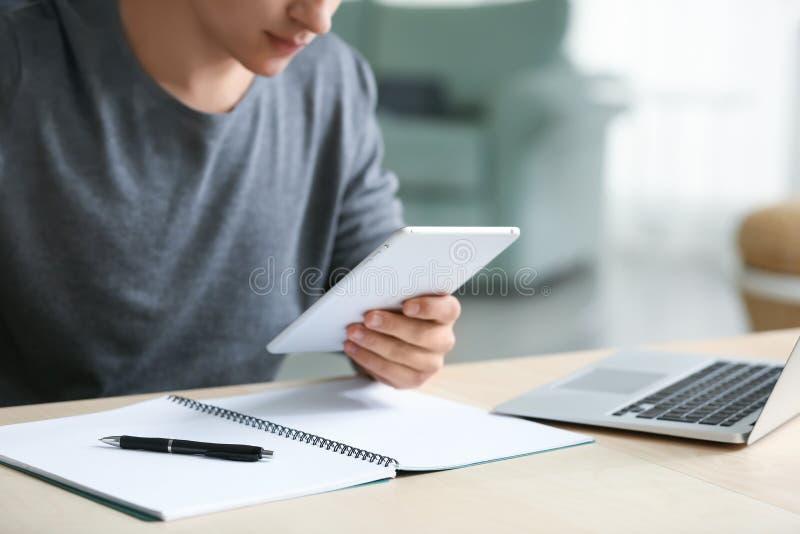 Junger Mann, der mit Tablet-PC im Innenministerium arbeitet lizenzfreies stockfoto