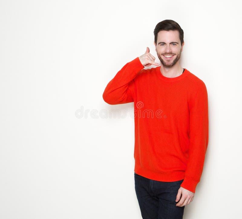 Junger Mann, der mit Telefonhandzeichen lächelt stockfoto